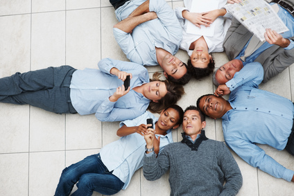 Business colleagues lying in circle doing various activities